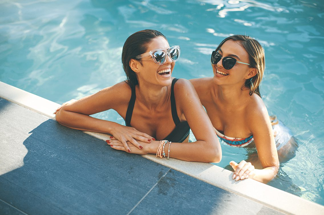 Young women having fun by the pool at hot summer day